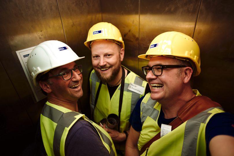 Drei Männer in einem Fahrstuhl. Schön warm war es.